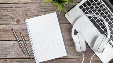 Headphones over laptop and notepad